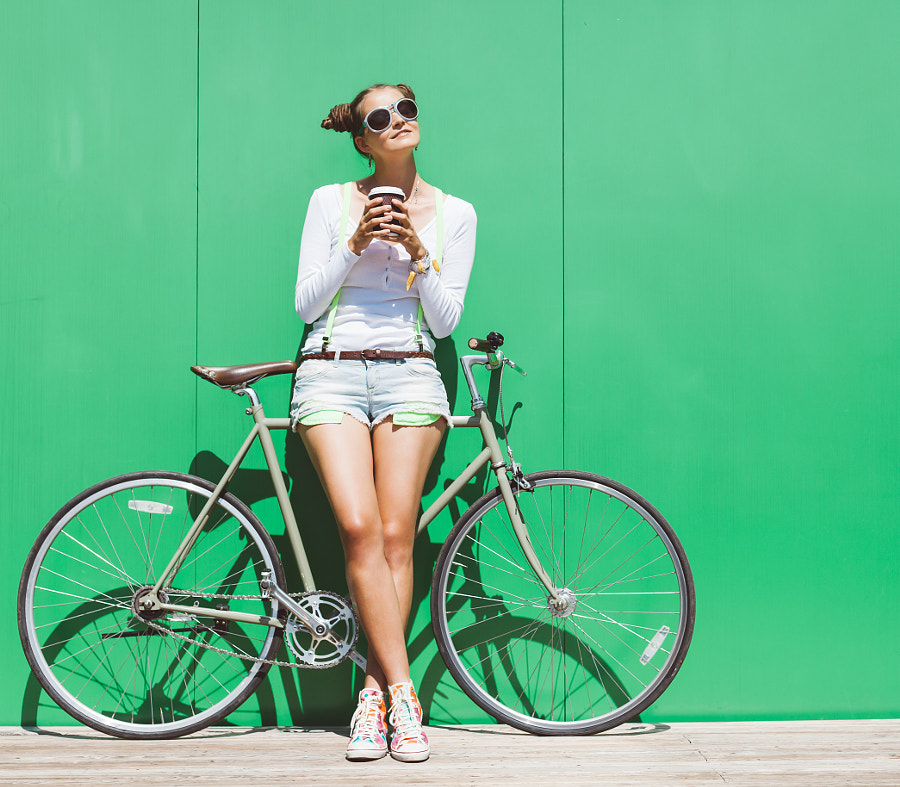 Fashionable beautiful young Pretty girl in shorts and t-shirt and sunglasses stands with  bicycle fi by Alexander Alenin on 500px.com
