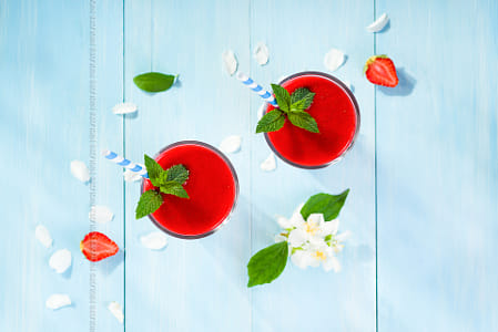 Strawberry smoothie and flower petals on blue background top vie by Kimberly Potvin on 500px