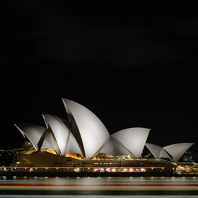 Late night view of the Sydney Opera House and a passing ferry