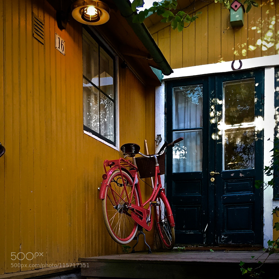 Red bike by a yellow house on a green island in the blue sea