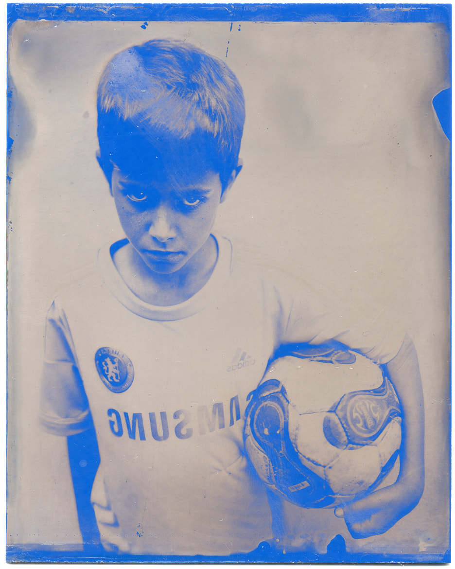 Photograph Rhys holding football on blue wetplate. by Sam Cornwell on 500px