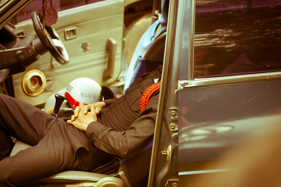 Police officer taking a nap in the car by Julien Vernet