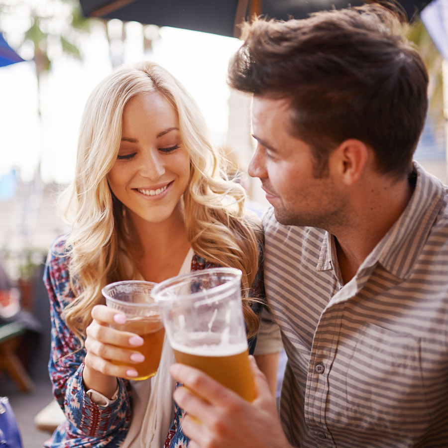 romantic couple drinking beer in outdoor pub or bar making a toast by Joshua Resnick on 500px.com