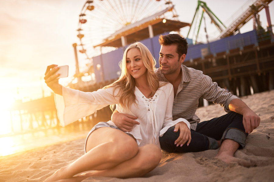 couple poses - romantic couple taking selfie together at santa monica near sunset by Joshua Resnick on 500px.com