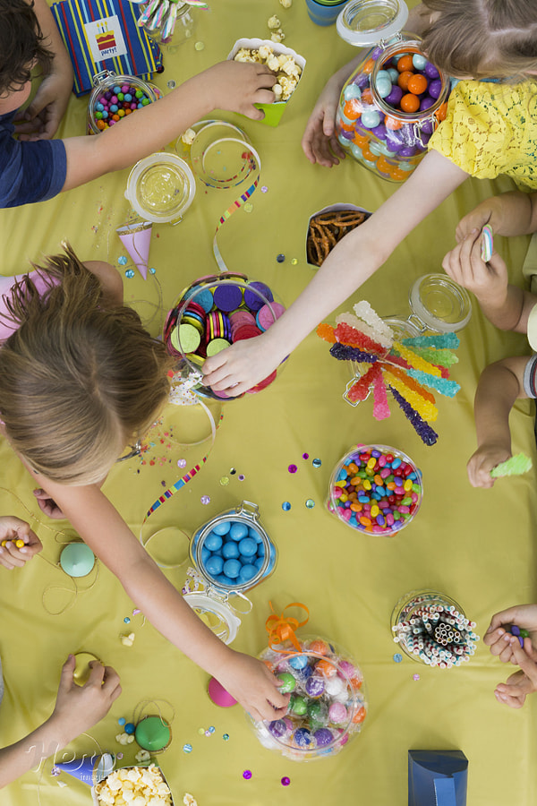 Overhead view kids reaching candy table birthday party by Hero Images on 500px.com