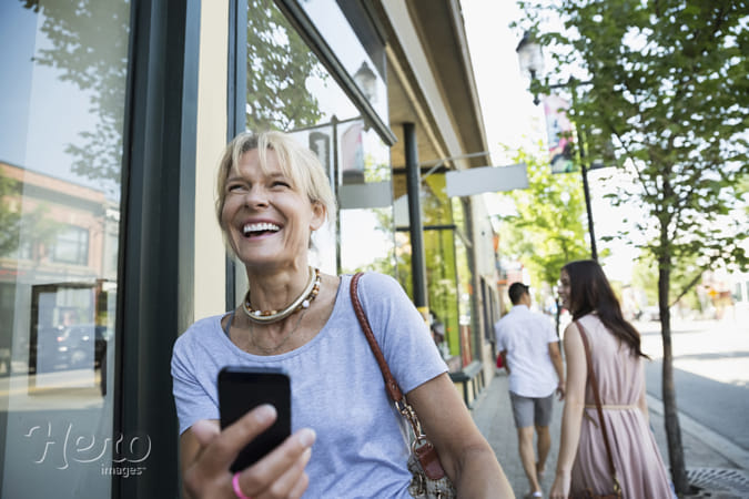 Laughing woman with cell phone at storefront