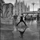 a waiter of a coffee bar in piazza duomo, milano, is jumping over a large puddle after a springtime rain shower