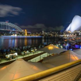 Busy night at the Opera Bar in front of the Sydney Opera House and Harbour Bridge