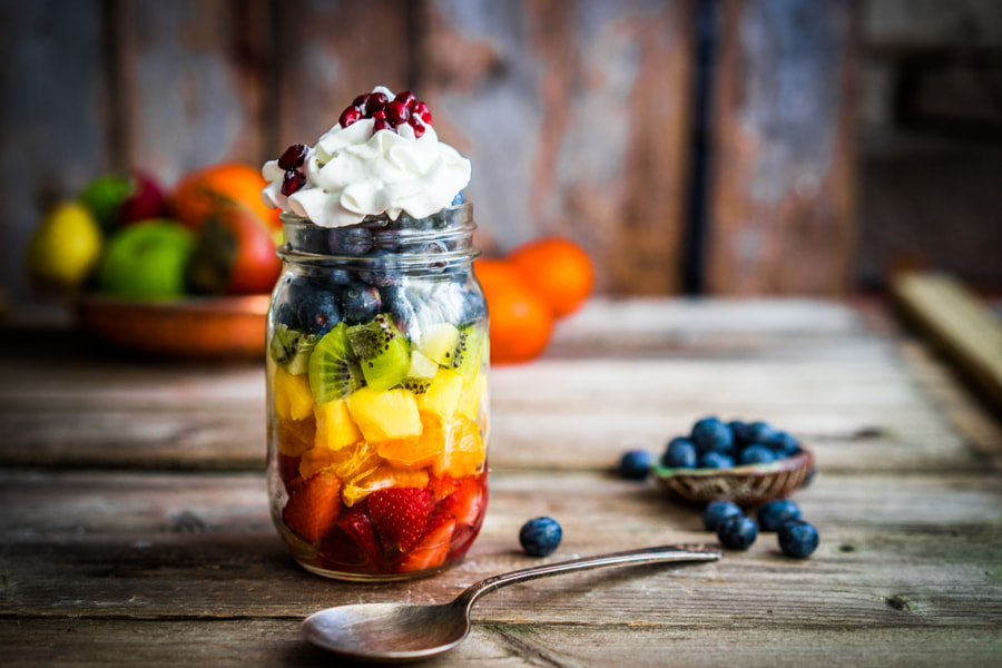 Colorful fruit salad in a jar on rustic wooden background by Alena Haurylik on 500px.com