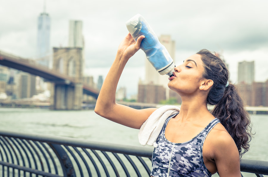 Thirsty athlete drinking after long run in New york city. Brooklyn bridge and skyline in the backgro by Cristian Negroni on 500px.com