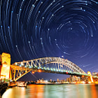 This is my second attempt in taking star-trail photo over the Harbour Bridge. To avoid light pollution from the city, 185 photos of stars were taken at this location in a new moon night with totally clear dark sky. Technically, each shot was captured with f4.0, 90 seconds, iso 200 at 18 mm. To keep the bridge sharpness, I took another shot with f16.0, 420 seconds. 