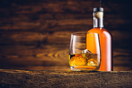 Whiskey glass and bottle on the old wooden table by Brian Wilson on 500px