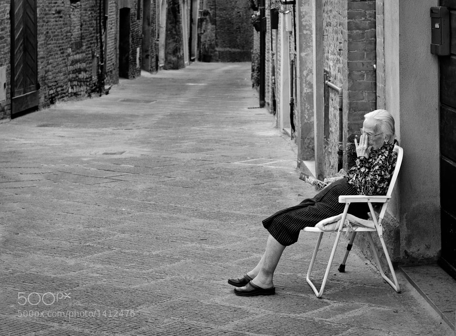 An old woman sits outside her house in a deserted Italian street
