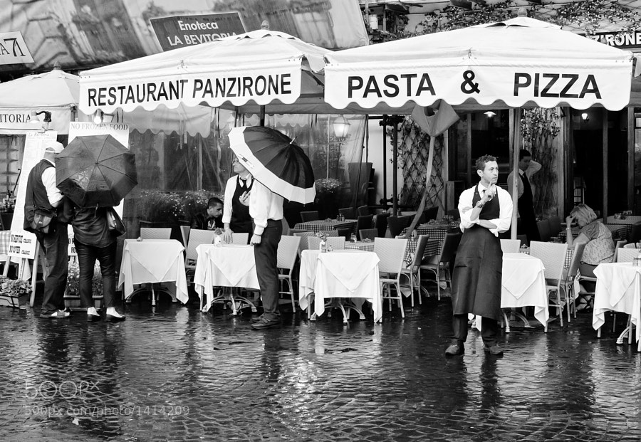 Waiters outside restaurant on a rainy Roman day