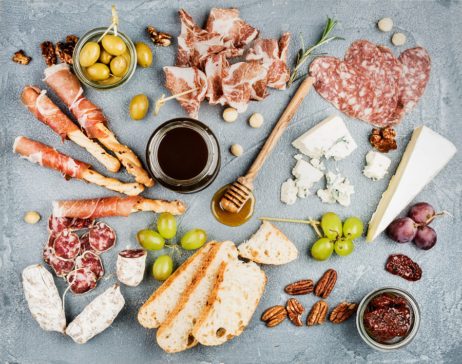 Cheese and meat appetizer selection or wine snack set. Variety of  cheese, salami, prosciutto,..., автор — Anna Ivanova на 500px.com