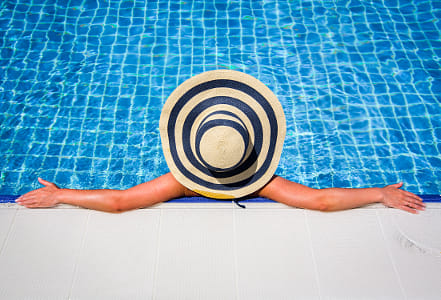 Woman in straw hat relaxing swimming pool by Kimberly Potvin on 500px