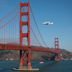Space shuttle Endevour flying over the Golden Gate bridge in San Francisco.