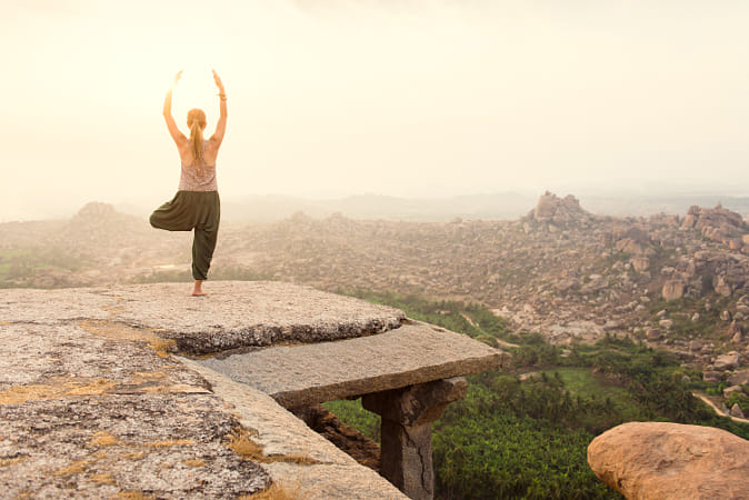 Young woman practicing yoga at mountain cliff on sunrise by Janet Weldon on 500px