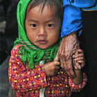 This child was holding her grandmothers hand at a remote markets in Dong Van, North Vietnam.
