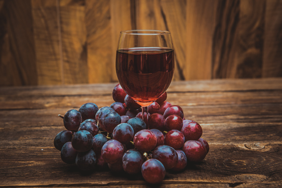 glass of wine or grape juice and fruit on wooden table by JTA on 500px.com