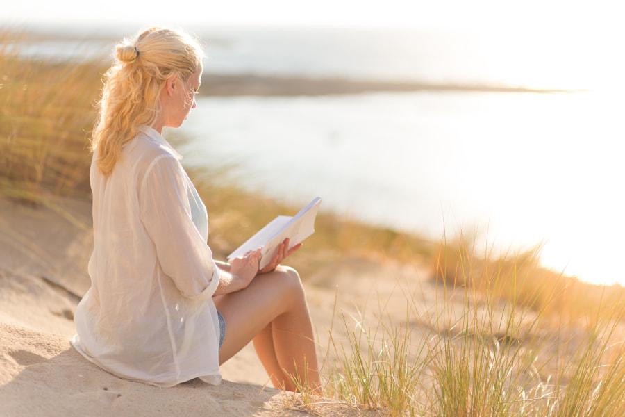 Woman enjoys reading on beautiful sandy beach. by Matej Kastelic on 500px.com