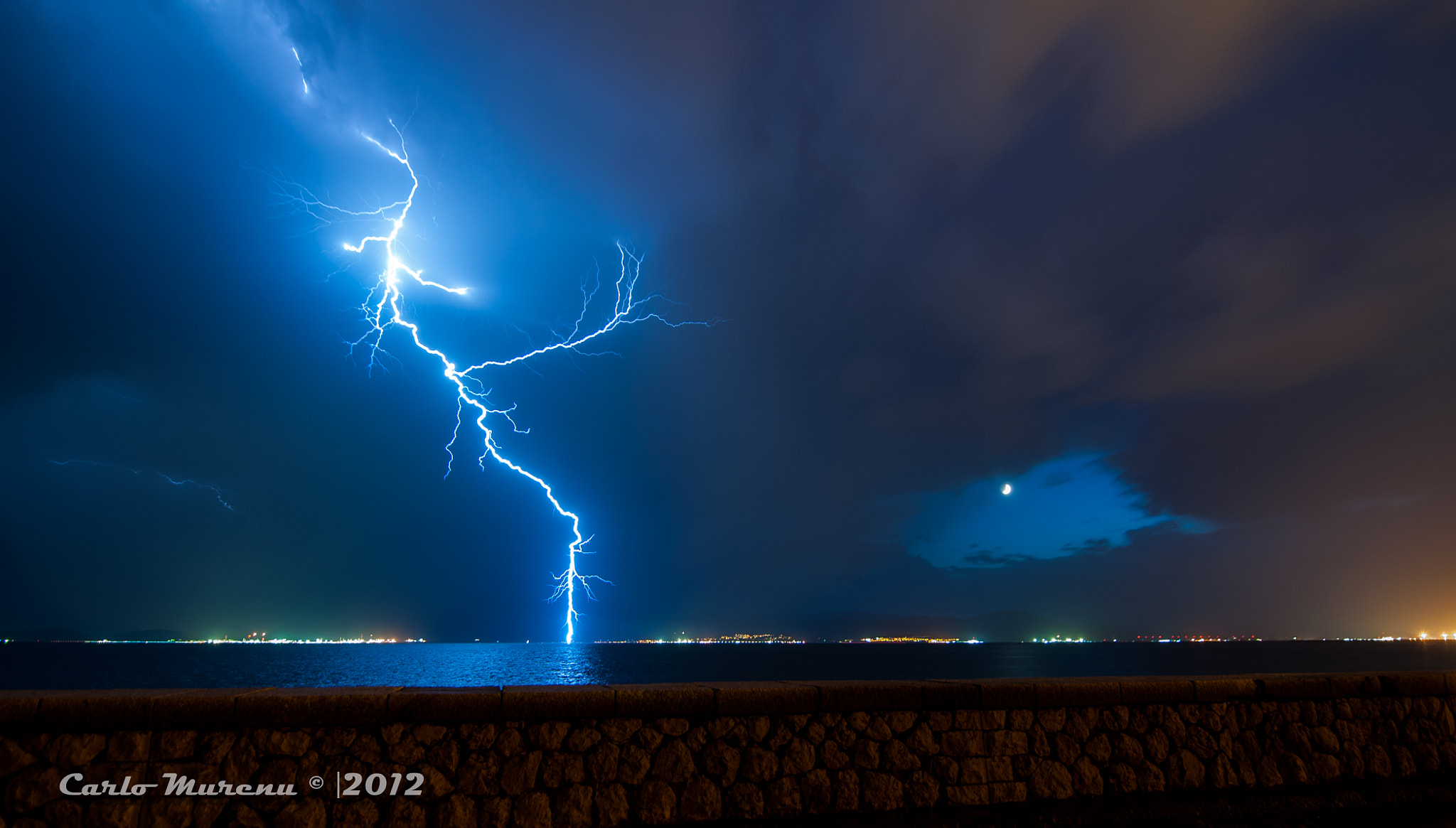 Photograph The daring bolt and distant moon by Carlo Murenu on 500px