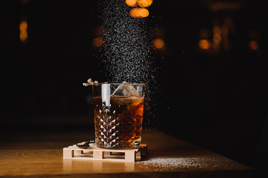 dusting whiskey drink with  ice  on  wood in bar by Maksym Fesenko on 500px.com