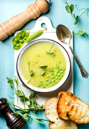Light summer green pea cream soup in bowl with sprouts, bread toasts and spices by Heather Balmain on 500px