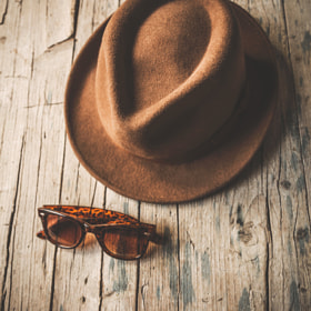 Sunhat and sunglasses on wooden table