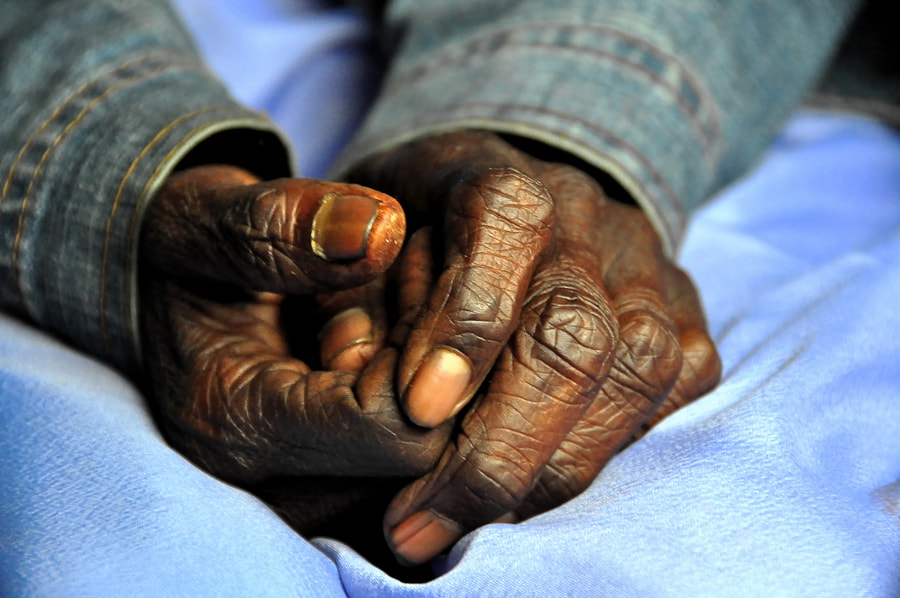 Detail of the hands of a man travelling on a train in Sri Lanka