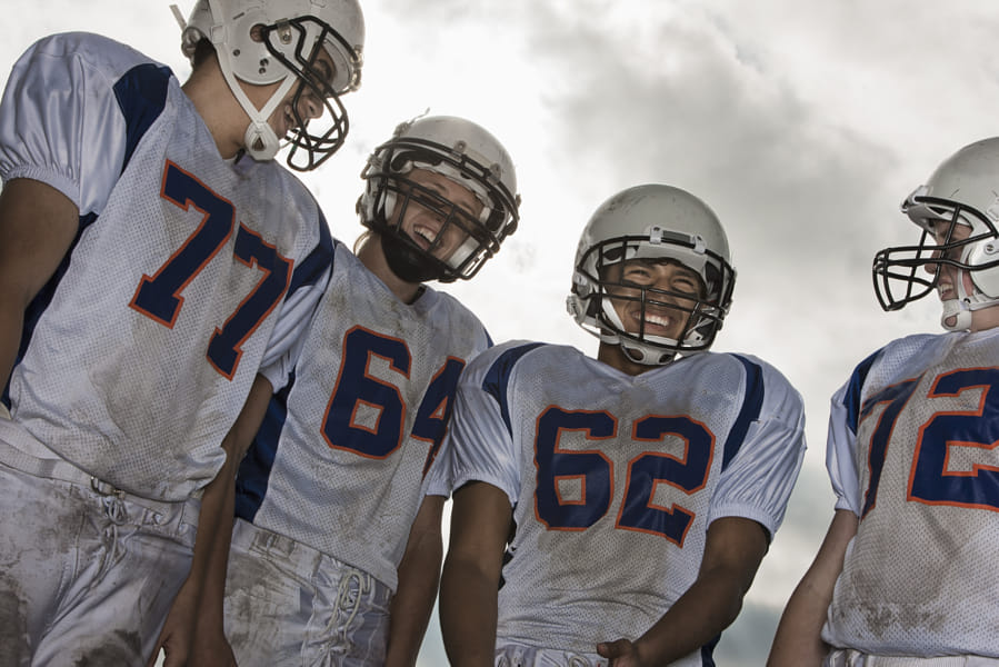A group of football players, members of a squad, young people in sports uniform and protective...