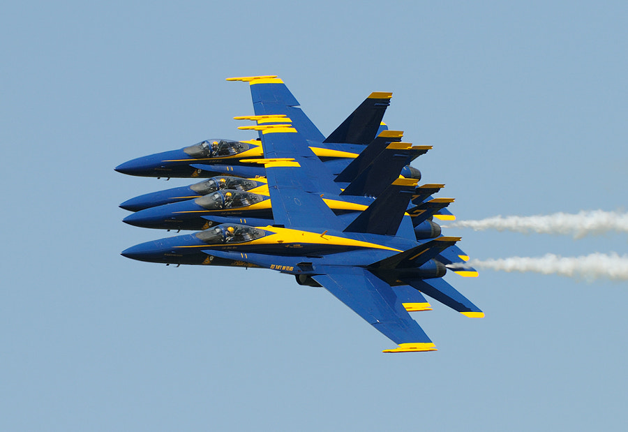 Close flying at its best performed by the fantastic pilots of the US Navy's Blue Angels. Number 1 in front is Flight Leader and Commanding Officer Commander Dave Koss. Number 2 next to him is Lieutenant Commander Jim Tomaszeski. Number 3 next to Jim Tomaszeski is Major Brent Stevens, and last, but not least, Number 4 is Lieutenant Rob Kurrle, Jr. You also can see clearly how the three pilots behind there Leader are looking at there neighbors.  Best regards, Harry