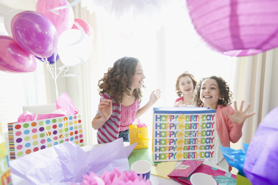 girls opening gifts at birthday party by Hero Images on 500px.com