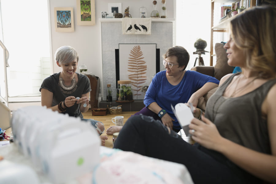 Women talking and packaging crafts in living room