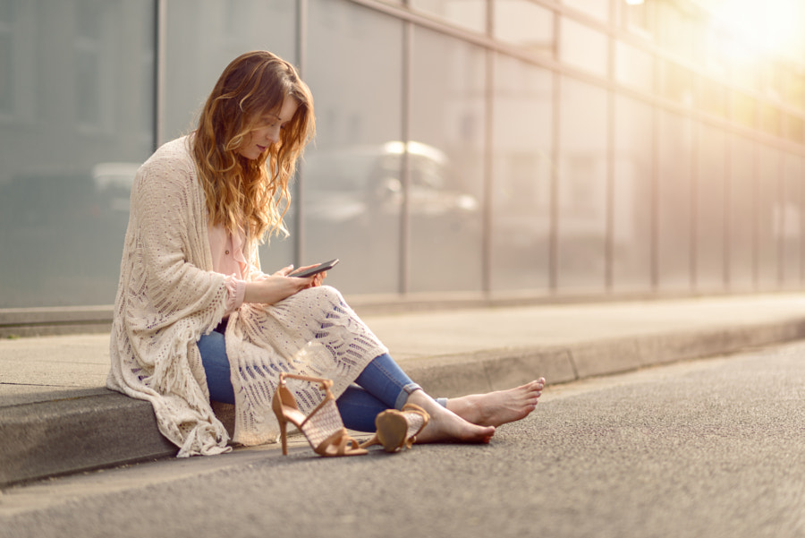 Attractive woman sitting on the kerb of a street by Lars Zahner on 500px.com