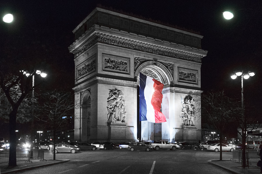 Arc de Triomphe by night with the french flag.