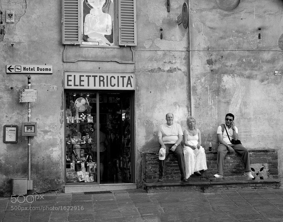 A family takes a break outside an electric shop in Siena, Italy