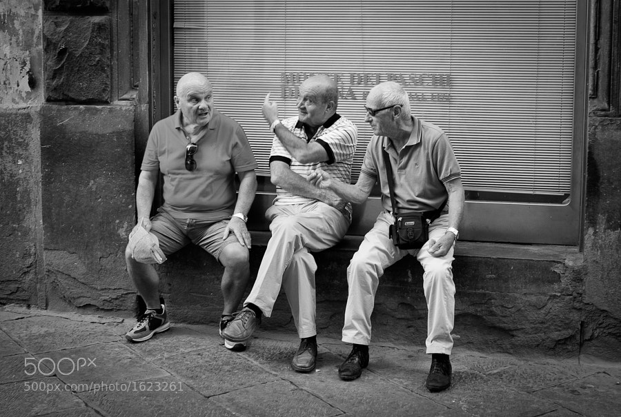 Three men discuss life and love on the streets of Siena, Italy