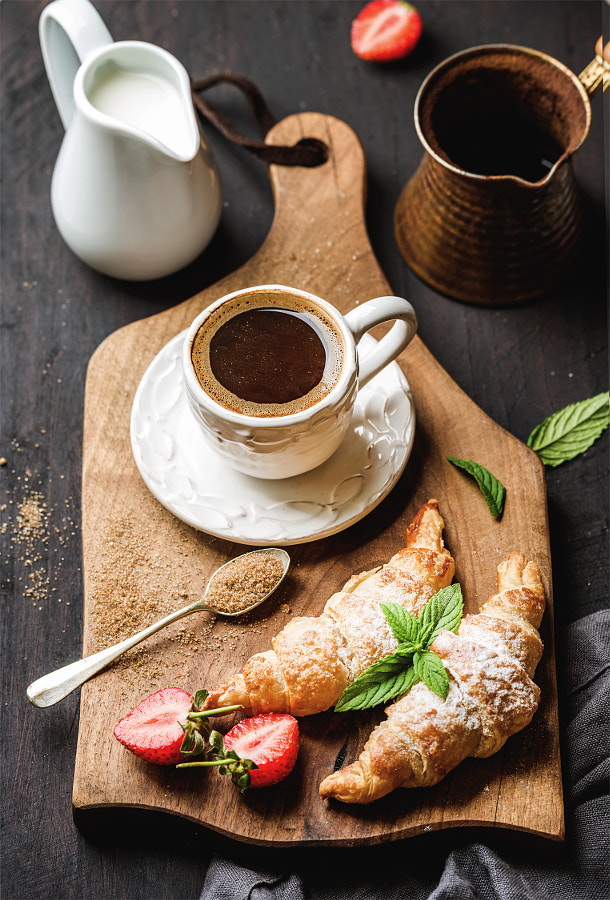 Breakfast set. Freshly baked croissants with strawberry, mint leaves and cup of coffee on wooden..., автор — Anna Ivanova на 500px.com