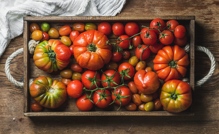 Colorful Heirloom tomatoes in rustic wooden tray over dark background by Anna Ivanova on 500px.com