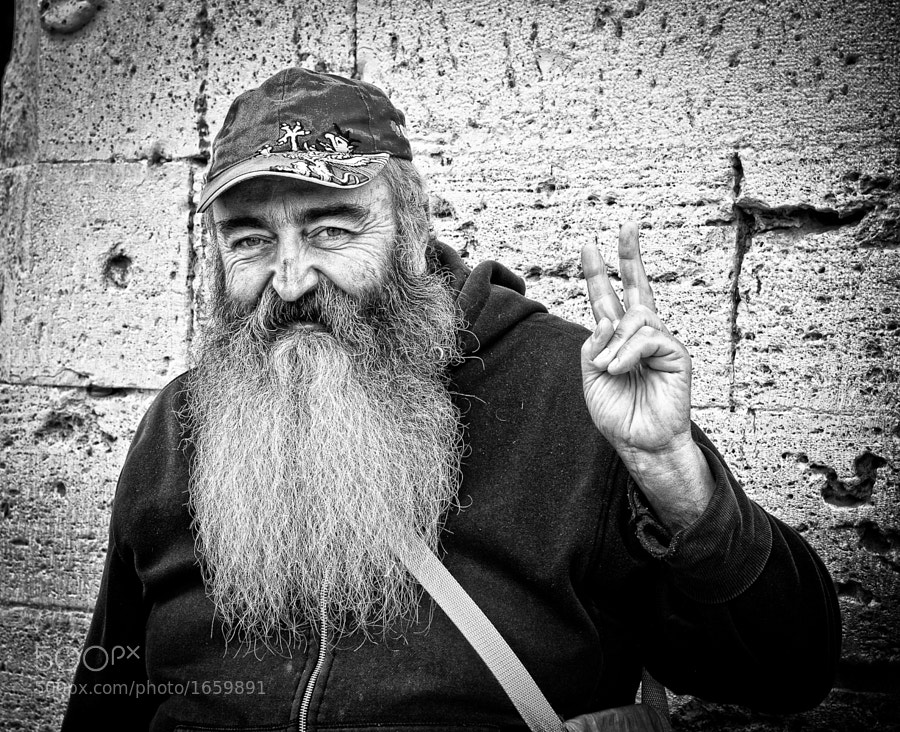 An elderly bearded man makes a peaceful sign