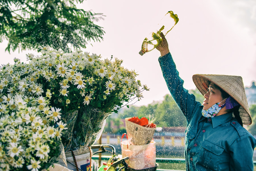 Flower vendor waters the flower by Quang Vu on 500px.com