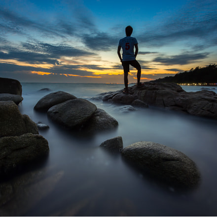 A handsome guy stand on rock with smooth wave