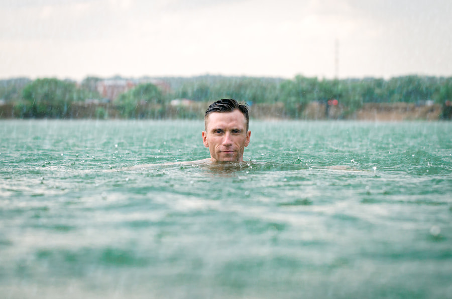 Man swimming in lake under the rain in thunderstorm by Bogomyakov Sergey on 500px.com