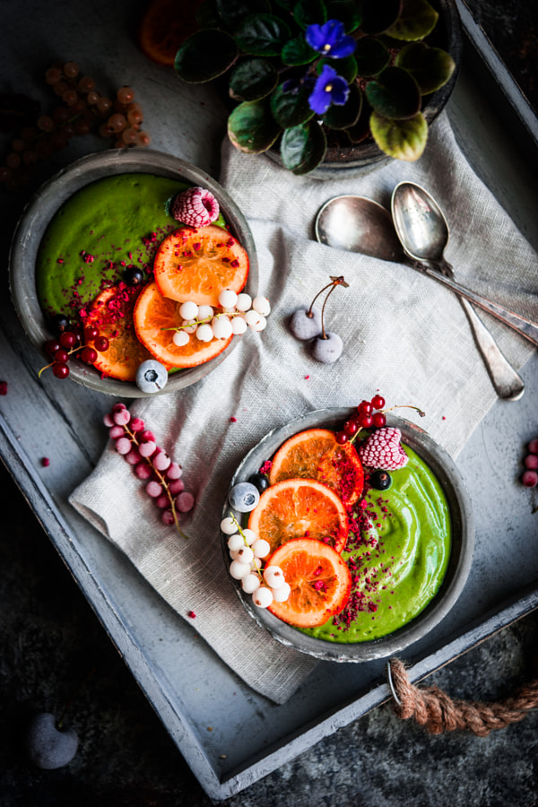 Green smoothie bowl with fruits and berries on rustic background by Alena Haurylik on 500px.com