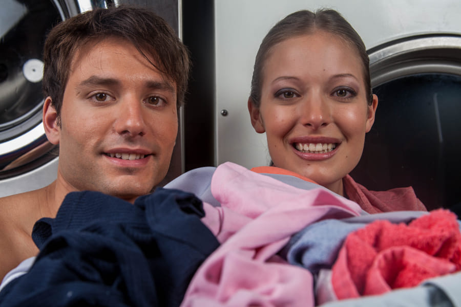 Man and woman looking at camera in the laundry