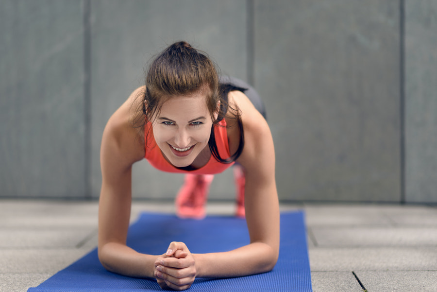 Fit young woman doing planks by Lars Zahner on 500px.com