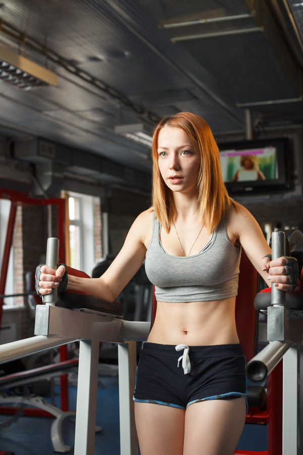 Young strong girl do leg lift for abs in gym by Denis Kornilov on 500px.com