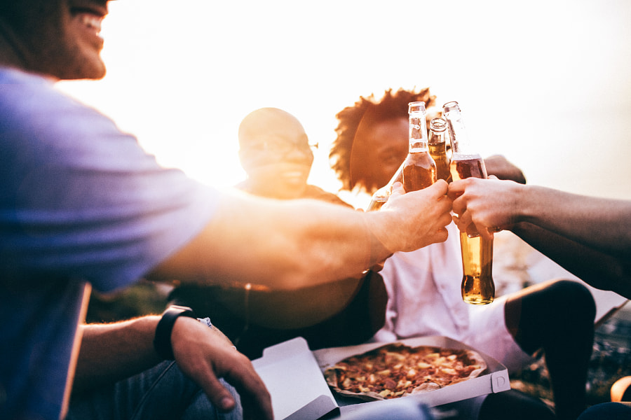 Friends celebrating and toasting with beer bottles by Carina König on 500px.com