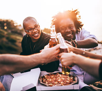 Friends celebrating with beer and pizza at picnic by Alejandro Santiago on 500px